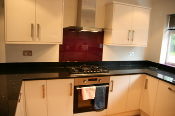 Star Galaxy worktops with red glass splash backs and window sill.Granite work tops Farnham Surrey