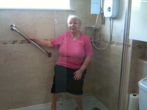 Margaret trying out her new seat in the shower