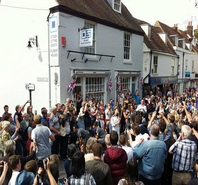 Picture of large gathering of people outside leydon shop to watch Olympic torch being lit
