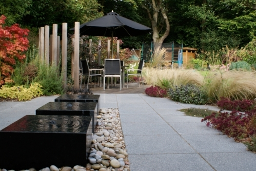 Rosemary Coldstream - Paved terrace, with water feature, seating area surrounded by ornamental grasses